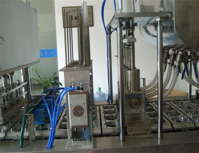 close-up photo of cups filling sealing machines automatic.jp